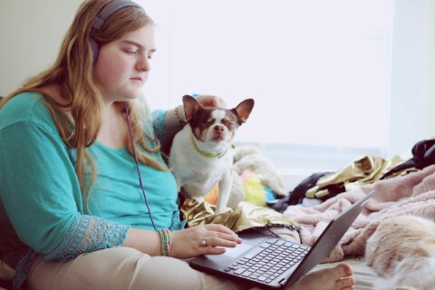 person sitting with a laptop on their lap and a dog next to them