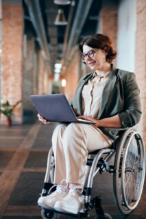 person in wheelchair with laptop computer